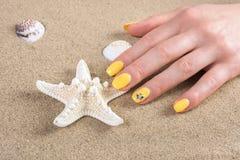 Frau mit gelben Nägeln maniküren Politur rührende Starfish auf Meersand auf Strand stockbilder