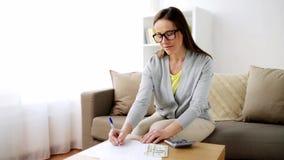Frau mit Geld, Papieren und Taschenrechner zu Hause stock video footage