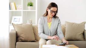 Frau mit Geld, Papieren und Taschenrechner zu Hause stock footage