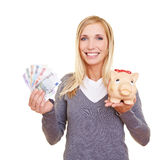Frau mit Geld und piggy Querneigung lizenzfreies stockbild