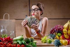 Frau mit Geldbargeld und gesundem Lebensmittel stockfotografie