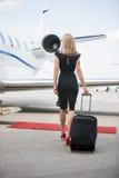 Frau mit Gepäck gehend in Richtung zum Privatjet Lizenzfreie Stockfotografie