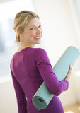 Frau mit gerollt herauf Übung Mat In Gym Lizenzfreies Stockfoto