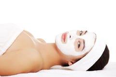Frau mit Gesichtslehmmaske. Lizenzfreies Stockbild