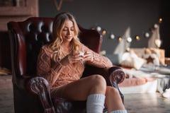 Frau mit Getränk im Lehnsessel Stockbild