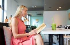 Frau mit Getränklesebuch am Café Stockfotos
