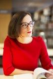 Frau mit Gläsern in der Bibliothek mit Buch Stockbild