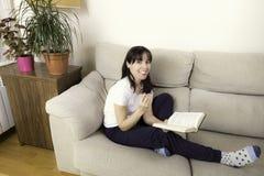 Frau mit Gläsern ein Buch auf einem Sofa lesend stockbild