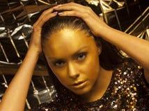 Frau mit goldenem Make-up und bodyart Stockfoto