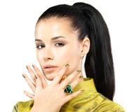 Frau mit goldenen Nägeln und Edelsteinsmaragd Stockfoto