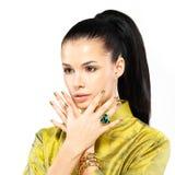 Frau mit goldenen Nägeln und Edelsteinsmaragd Stockfotografie
