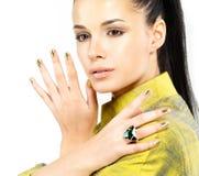 Frau mit goldenen Nägeln und Edelsteinsmaragd Lizenzfreie Stockbilder