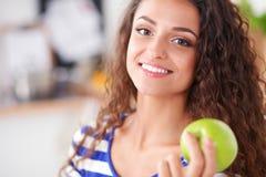Frau mit grünem Apfel und Laptop, der in der Küche sitzt Stockfoto