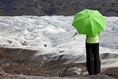 Frau mit grünem Regenschirm durch Glacier lizenzfreies stockbild