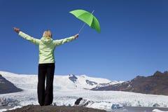 Frau mit grünem Regenschirm nahe bei Gletscher Lizenzfreies Stockbild