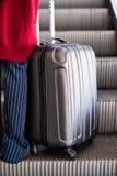Frau mit grauem Koffer auf Rolltreppe stockfotografie