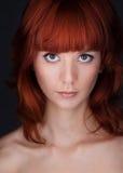 Frau mit großen Augen und dem roten Haar Stockbild