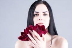 Frau mit großen Augen und glatte Hautfrau, die eine rote Blume hält Stockfoto