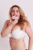 Frau mit großen Meisen isst ein buntes Muffin Stockfoto