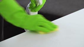 Frau mit Gummihandschuhen sprüht ein Reinigungsmittel und säubert es mit gelbem Schwamm stock footage