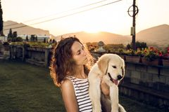 Frau mit Hündchen bei Sonnenuntergang lizenzfreie stockfotografie