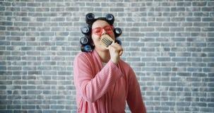 Frau mit Haarlockenwicklern, Gläsern und Bademantel singend in der Haarbürste, die Spaß hat stock video footage