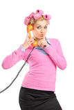 Frau mit Haarrollen sprechend an einem Telefon Lizenzfreie Stockfotos