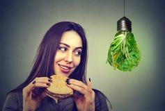 Frau mit Hamburger denkend an alternative Diätwahlen lizenzfreie stockfotos