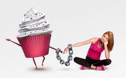 Frau mit Handschellen gefesselt zu einem kleinen Kuchen Stockbilder
