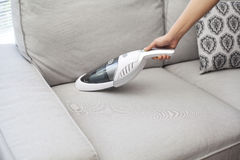 Frau mit HandStaub saugen auf Sofa stockfotografie