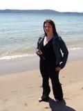 Frau mit Handy auf Strand Stockfoto