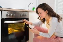 Frau mit Handy beim Kochen des Huhns Stockbild