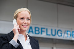 Frau mit Handy am Flughafen stockfotografie