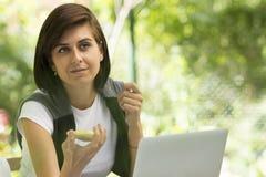 Frau mit Handy und Laptop lizenzfreie stockfotos