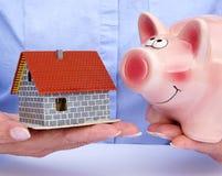 Frau mit Haus und Sparschwein Stockbild