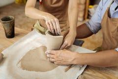 Frau mit helfendem Töpfer der dunklen Nagelkunst mit der Herstellung des Vase stockfotos