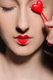 Frau mit Herzen auf Lippen und vor Auge Stockbild
