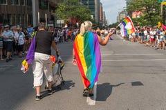 Frau mit homosexueller Flagge des Regenbogens auf ihr zurück stockfoto