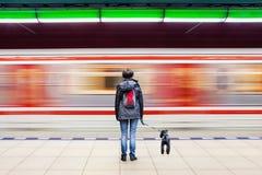 Frau mit Hund an der U-Bahnstation mit undeutlichem beweglichem Zug Stockfoto