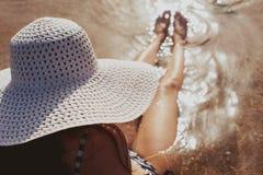 Frau mit Hut nahe Swimmingpool im tropischen Erholungsort Stockbilder