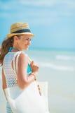 Frau mit Hut und Tasche an der Küste, die Abstand untersucht Stockfotos