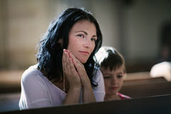 Frau mit ihrem betenden Sohn Stockbild