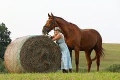 Frau mit ihrem Pferdeaufenthalt nahe Heurolle auf Wiese Lizenzfreies Stockfoto