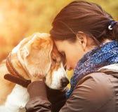 Frau mit ihrer Hundeangebotszene Stockfoto