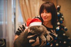 Frau mit ihrer Katze, die Santa Claus-Hut nahe Weihnachtsbaum trägt Stockbilder