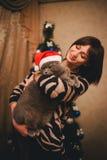 Frau mit ihrer Katze, die Santa Claus-Hut nahe Weihnachtsbaum trägt Lizenzfreie Stockfotos