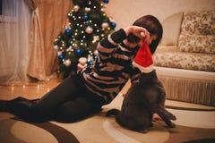 Frau mit ihrer Katze, die Santa Claus-Hut nahe Weihnachtsbaum trägt Stockbild
