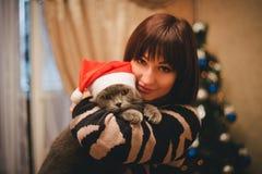 Frau mit ihrer Katze, die Santa Claus-Hut nahe Weihnachtsbaum trägt Stockfotografie