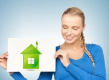 Frau mit Illustration des grünen Öko-Hauses Stockbild