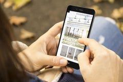 Frau mit Innenarchitekturwebsiteentwurfstelefon im Park lizenzfreie stockfotografie